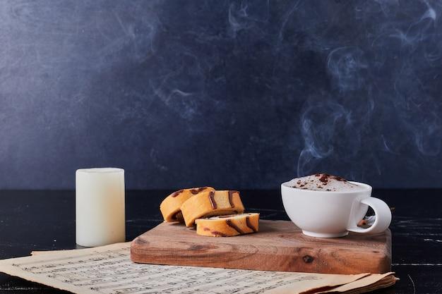 コーヒーパウダーとロールケーキと牛乳のカップ。
