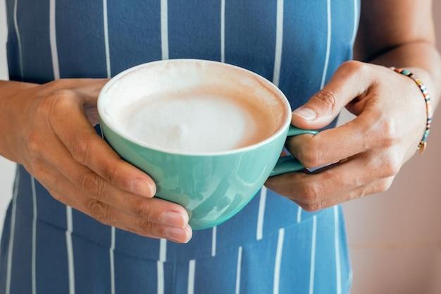 若い女性の手に朝のコーヒーのカップ