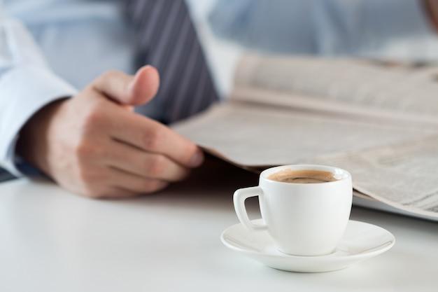 新聞を保持しているビジネスアナリストと朝のコーヒーのカップ