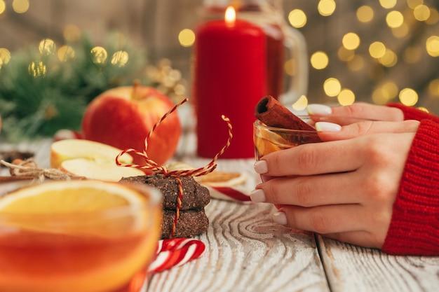 木製のテーブルに女性の手でグリューワインのカップ