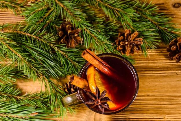 素朴な木製のテーブルにシナモンとモミの木の枝とホットワインのカップ。上面図