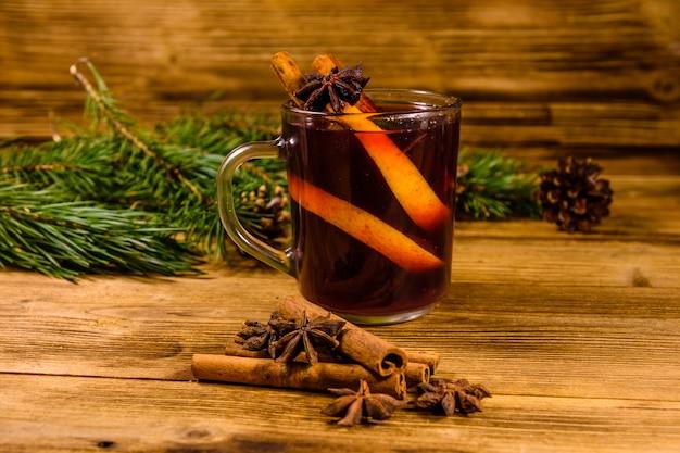 素朴な木製のテーブルにシナモンとモミの木の枝とホットワインのカップ