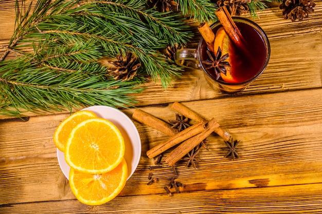 素朴な木製のテーブルにシナモン、スライスしたオレンジとモミの木の枝とホットワインのカップ。上面図