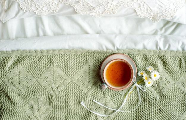 Чашка натурального травяного чая из мяты и мелиссы в постели, утро крупным планом. уютная атмосфера. ажурное кружево, хлопковое белое одеяло, летние цветы ромашки. завтрак. прованс и ретро.