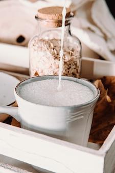 아늑한 컵에 무디 톤의 귀리 우유 한잔