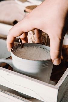 손으로 잡는 귀리 우유 한잔, 아늑한 컵에 변덕스러운 음색