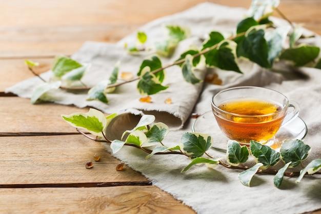 Чашка органического горячего зеленого чая на деревянном столе, копия космического фона