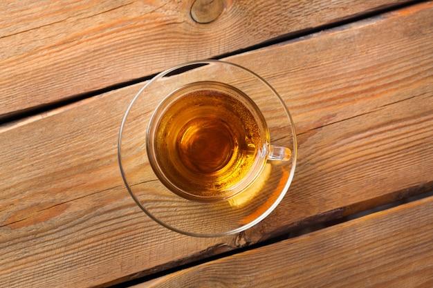 Чашка органического горячего зеленого чая на деревянном столе, копия пространства, плоский фон