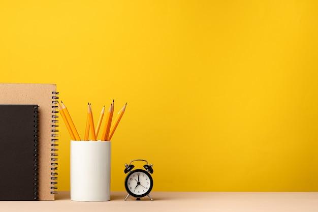 Чашка карандашей и блокнотов на столе против желтого,
