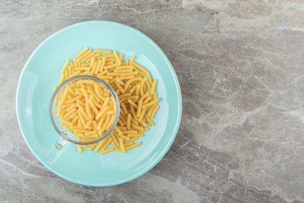 Чашка сырых макарон на синей тарелке