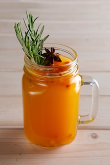 柑橘類、シナモン、ローズマリーと海クロウメモドキ茶のカップ