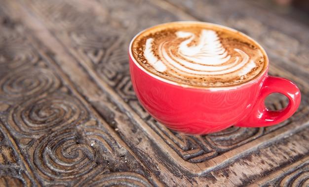 おいしいカプチーノのカップが木製の織り目加工のテーブルの上に立っています。ラテの上に素敵な白鳥が描かれています。カプチーノは赤いカップに入っており、孤立しています。