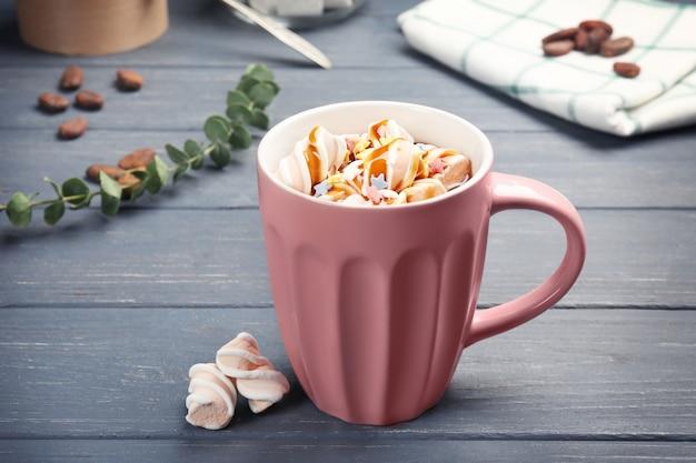 Чашка вкусного какао-напитка с зефиром на деревянном столе