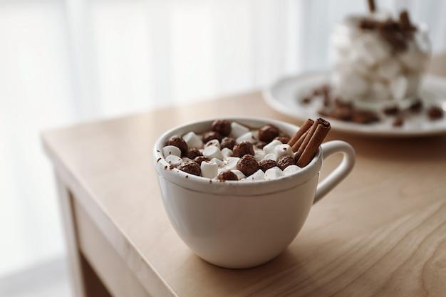テーブルの上にマシュマロとおいしいココアのカップ