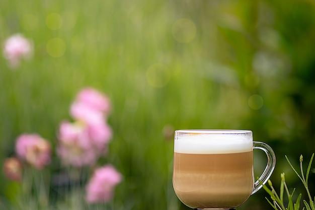 夏の庭を背景においしいコーヒーのカップ