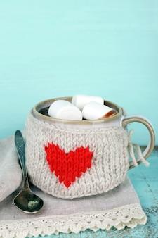 Чашка вкусного горячего какао, на деревянном столе, на цветном фоне