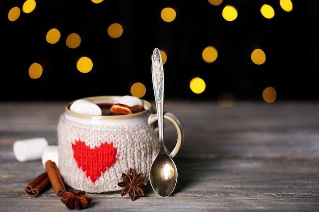 Чашка вкусного горячего какао, на деревянном столе, на блестящей поверхности