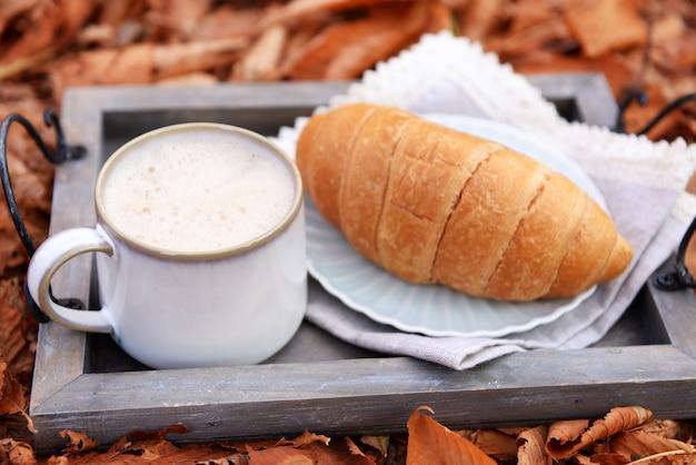 Чашка вкусного горячего напитка и свежий круассан на подносе, на пространстве осенних листьев
