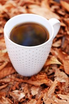 Чашка вкусного горячего напитка на поверхности осенних листьев