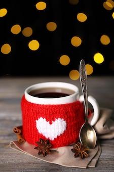 빛나는 배경에 나무 테이블에 맛있는 뜨거운 차 한잔