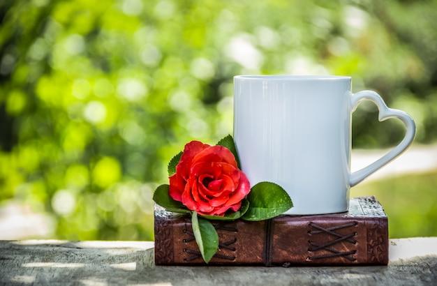 一杯のお茶と赤いバラ。