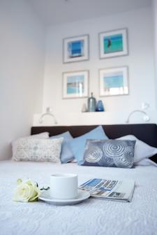 Чашка чая и белая роза лежат на кровати в ярком