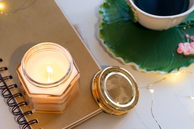 Чашка чая и ароматические свечи на тетради на белом столе