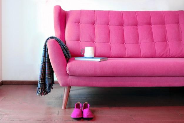 ピンクのコーチのお茶と青い本のカップは、リビングルームの居心地の良い家の家のインテリアで静物
