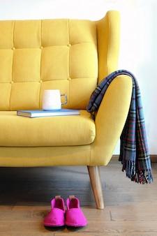 Чашка чая и синяя книга на деталях натюрморта желтого тренера в домашнем интерьере гостиной