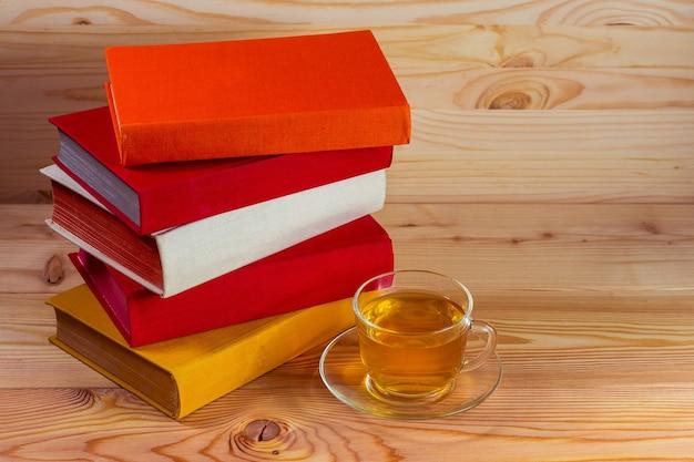 一杯のお茶と木製の背景の本