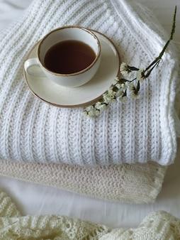 Чашка чая и ветка сушеных цветов на белом вязаном фоне