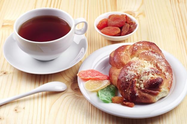 木製のテーブルにドライフルーツとお茶とパンのカップ