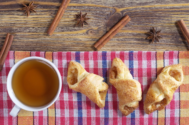 一杯のお茶と木製のテーブルにジャムとパン