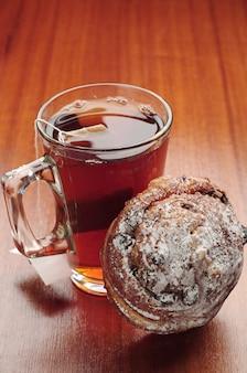 木製のテーブルにレーズンとお茶とパンのカップ