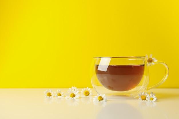 一杯のお茶とカモミールの黄色の背景に白いテーブル