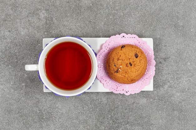 白い受け皿にお茶とチップクッキーのカップ