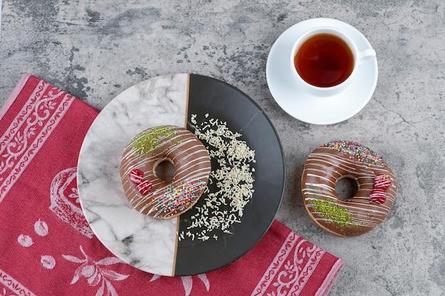 Чашка чая и шоколадные пончики с ягодами и посыпают мраморную поверхность.