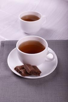 Чашка чая и шоколада с светлом фоне