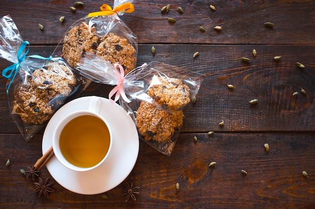 一杯の紅茶と木製のテーブルでクリスマスクッキー