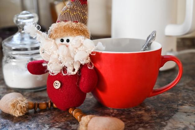 부엌 배경에 차와 크리스마스 그놈의 컵. 겨울 아침 휴가 개념입니다. 고품질 사진