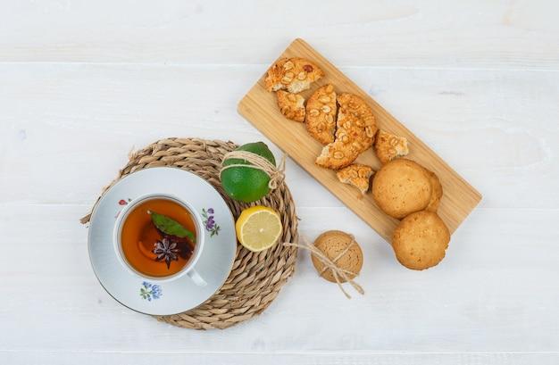 Чашка чая и цитрусовых с печеньем на разделочной доске на круглой подставке для посуды на белой поверхности