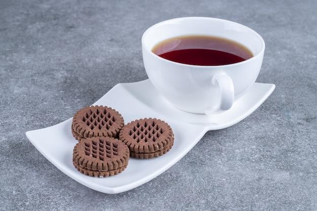白いプレートにお茶とココアビスケットのカップ