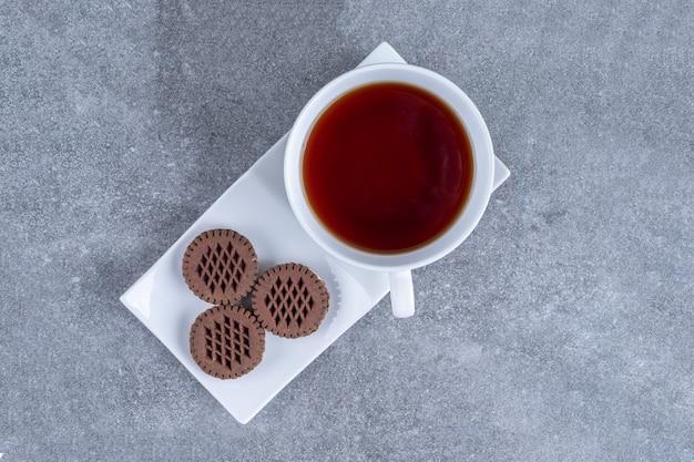 Чашка чая и какао-печенье на белой тарелке