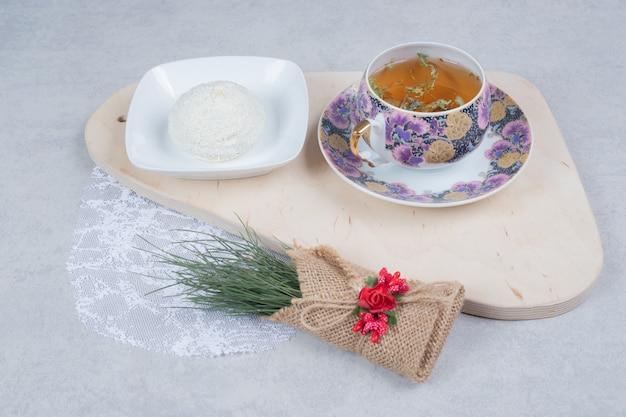 Чашка чая и кокосовое печенье на деревянной доске с рождественским украшением. фото высокого качества
