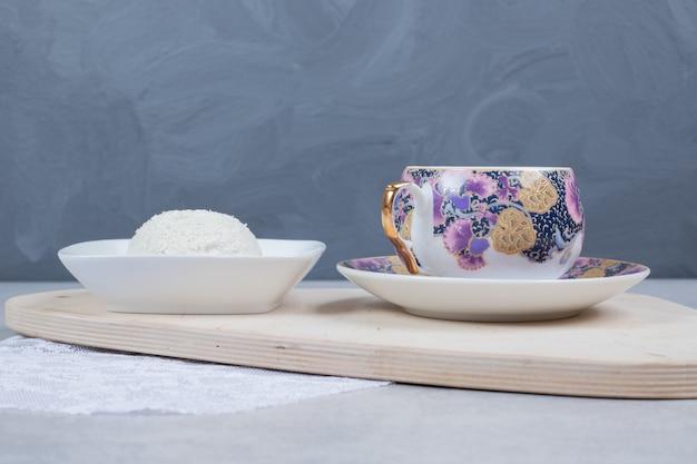 木の板にお茶とココナッツクッキーのカップ。
