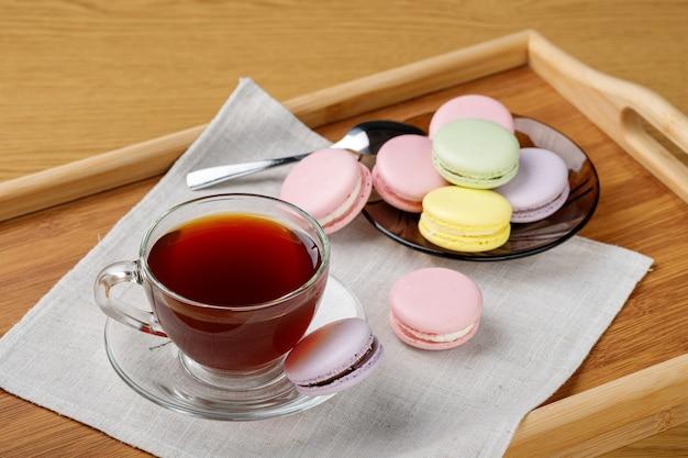 나무 쟁반에 차와 다채로운 마카롱 컵 아침 차와 과자