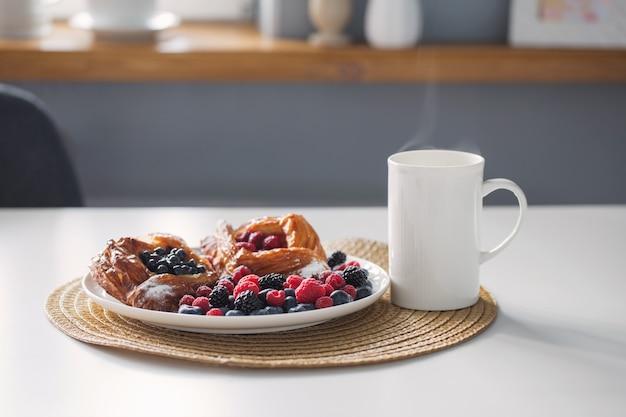 キッチンでベリーとお茶とデザートのカップ