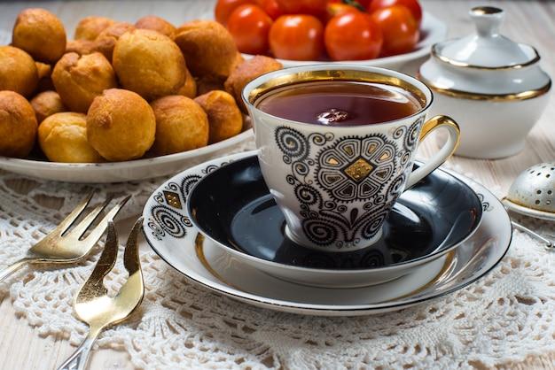 Чашка чая и пончики на деревянном столе