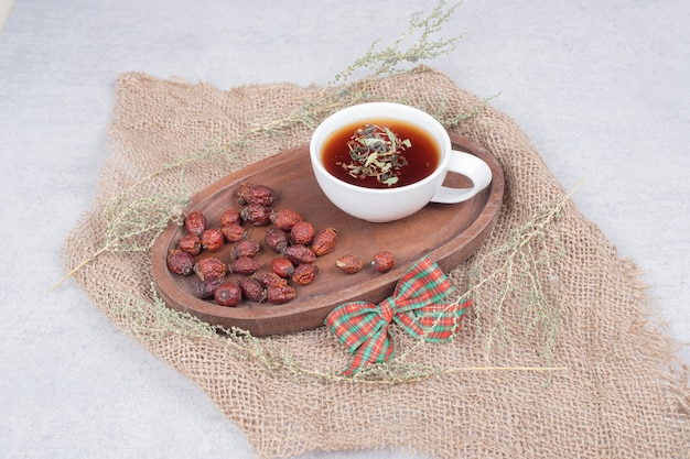 黄麻布にお茶とドライクランベリーのカップ。高品質の写真