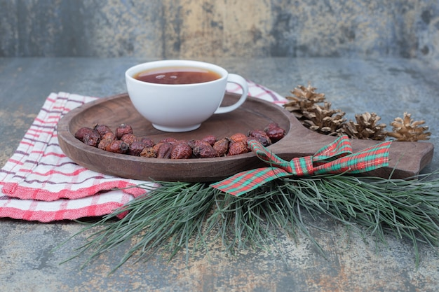 木の板にお茶と乾燥ローズヒップのカップ。高品質の写真